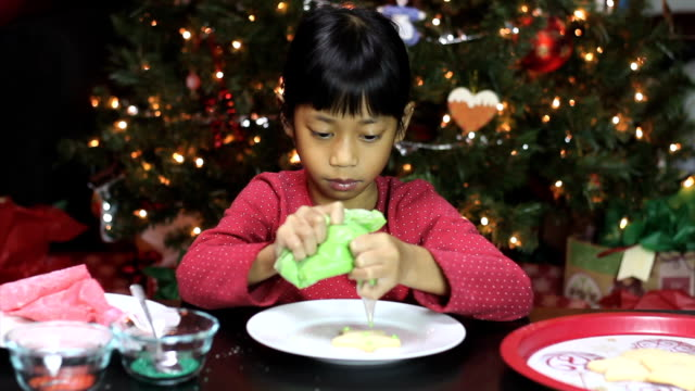 Asian Girl Adds Icing To Christmas Cookie video