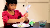 Asian Girl Adds Red Icing To Christmas Cookie video