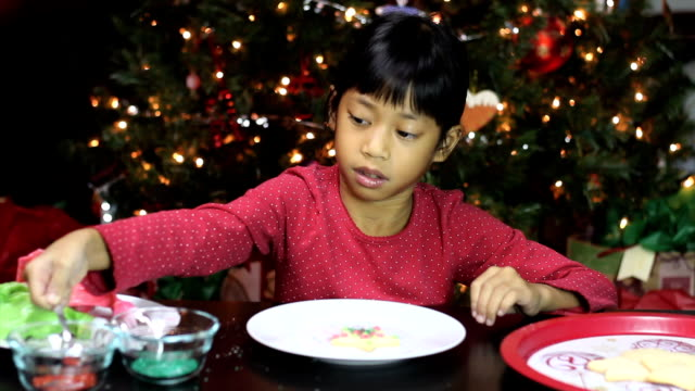 Asian Girl Adds Sprinkles To Christmas Cookie video