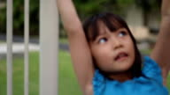 Asian girl climbs across the monkey bars at the playground video