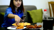 Asian girl eating pizza set and use telephone video