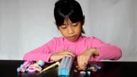 Asian Girl Enjoys Making A Bracelet On Her Loom video