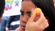 Asian Girl Getting A Rainbow Face Painting Mask Applied video
