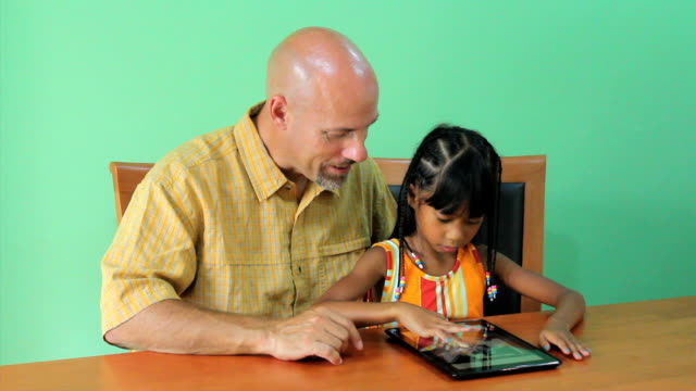 Asian Girl Learns How To Use Tablet With Father video