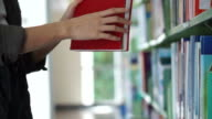 Asian girl looking for book, flip through and put back on library shelves video