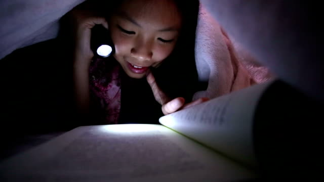 Asian girl reading a book in bed with flashlight video