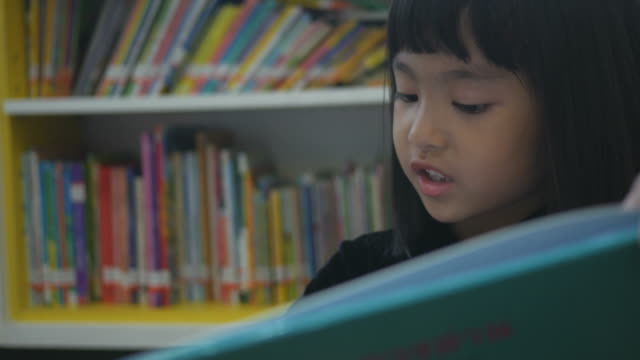 Asian girl reading book in library video