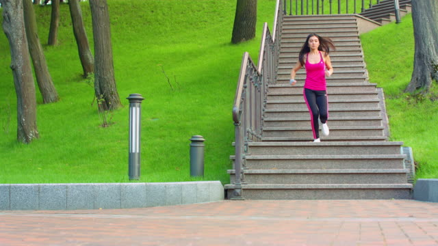 Asian girl running down stairs at park. Fitness model running downstairs video