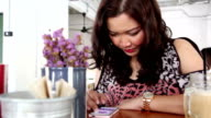Asian girl using app on smartphone in coffee shop video