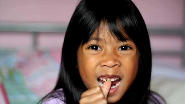 Asian Girl Wiggling Her First Loose Tooth video
