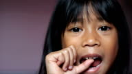 Asian Girl Wiggling Her First Loose Tooth-Close Up video