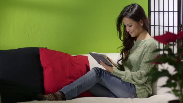 Asian girl with computer on sofa at home video