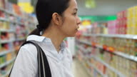 Asian girl, woman shopping snacks in supermarket video