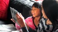 Asian Girls Enjoy Sharing Time On The Digital Tablet video