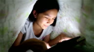 Asian girls play on tablet on the bed. video