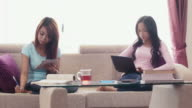 Asian girls using ipad, phone and studying at home video
