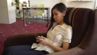 Asian happy woman texting message on smartphone sitting on the armchair video
