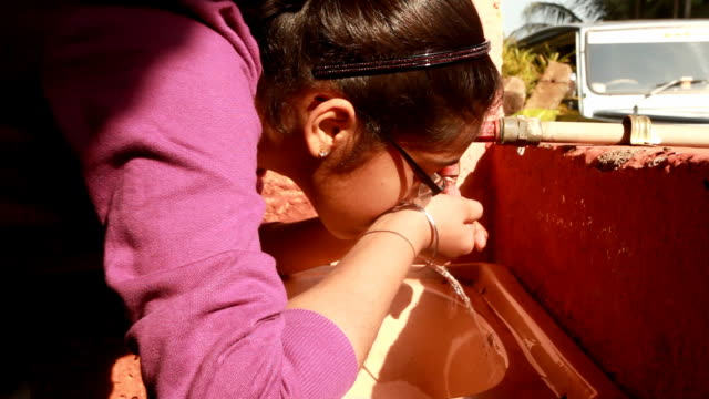Asian Indian Teenager girl drinking water from tap video