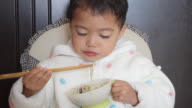 asian kid learning using chopsticks unskillfully to eat noodles video