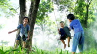 HD: Asian kids having fun playing on the swing under the tree in countryside video