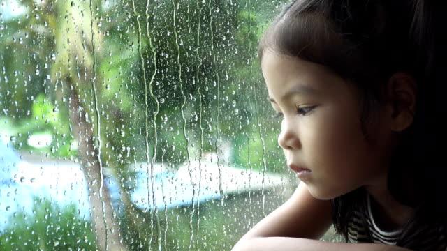 Asian little girl look at rain in a window, slow motion. video