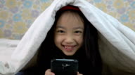 Asian little girl using smartphone under the blanket video