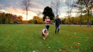 Asian man and Caucasian woman running in the park with his dog. Happy together, laughing video