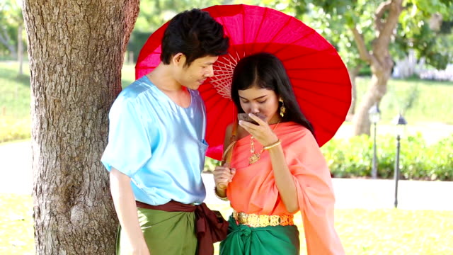 Asian man and woman in traditional Thai dress video