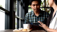 Asian man and woman talk together in coffee cafe video