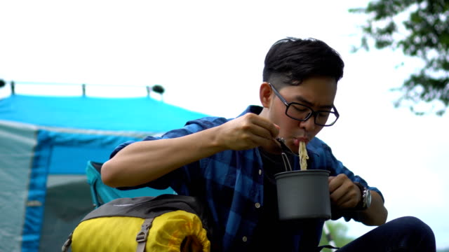 Asian Man eating instant noodle in countryside-camping area video
