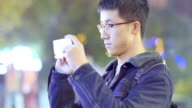asian man student holding mobile phone in campus at night video