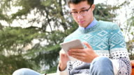 asian man student holding tablet in park video