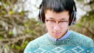 asian man student with headset in park video