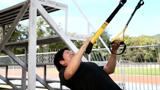 Asian man train his chest by using rope exercise video