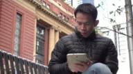 Asian man using digital tablet. Melbourne, Australia. video