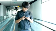 Asian man using his smart phone on a moving walkway/travelator. video