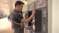 Asian man using public phone at airport video