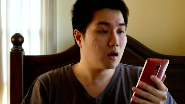 asian man waking up late for work, looking time on mobile phone video