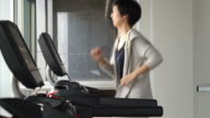 Asian mixed race sporty woman jogging on treadmill in gym, exercise and fitness concept video