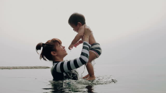 Asian Mother And Child Having Fun In Pool video