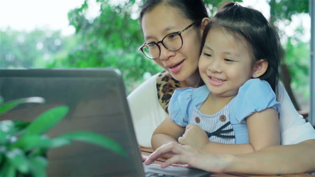 Asian Mother and Daughter using Laptop at the garden video