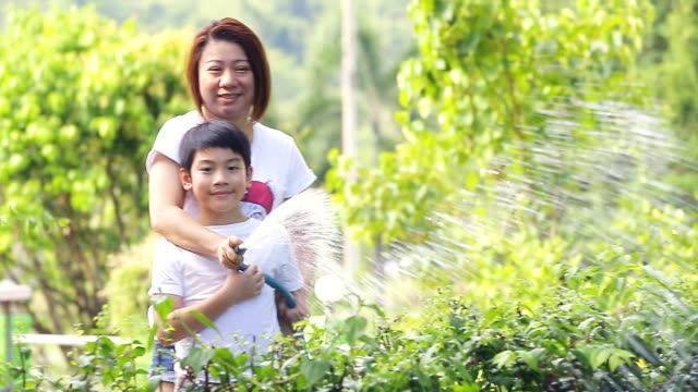 Asian mother and son are watering the tree video