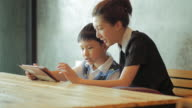 Asian mother and son using tablet computer video