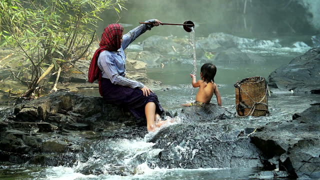 HD: Asian mother giving a kid a bath in the river video