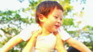 HD: Asian mother playing spinning in the air with little boy in the park at sunset. video