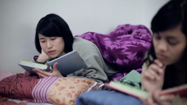 Asian multi ethnic college girls studying in bed. video
