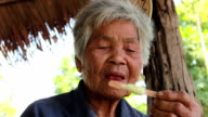 Asian old woman eating ice cream. video