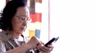 Asian old woman using a smart phone video