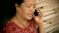 Asian people: A mature woman happily talking on mobile phone. video