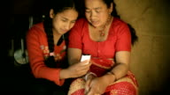 Asian people: Daughter showing mobile phone to her mother video